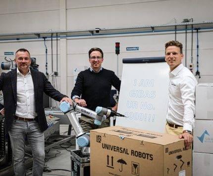 Drie mannen poseren voor een foto om te vieren dat er 1000 cobots van Universal Robots zijn verkocht